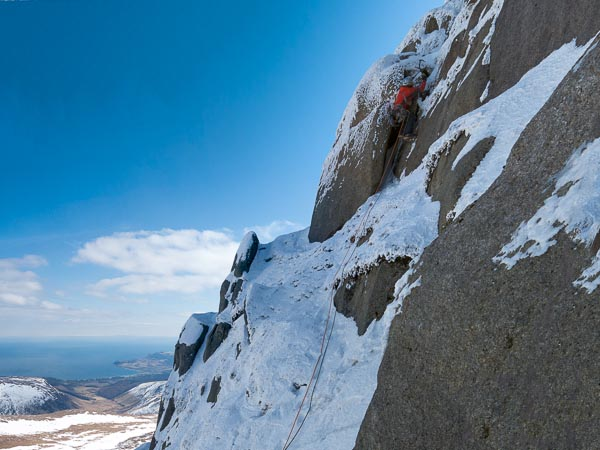 Stuart McFarlane climbing the final chimney on After the Storm (VI,5) on Beinn Nuis. Glen Rosa, Brodick and the Scottish mainland can be seen in the far distance. (Photo Simon Richardson)