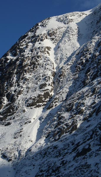 The upper 200m of The Gully (IV,4) on the Alladale Slabs. The photo shows the route above the easier snow slopes with the line cutting out right before the open snow gully to follow the drainage. (Photo Steven Andrews)