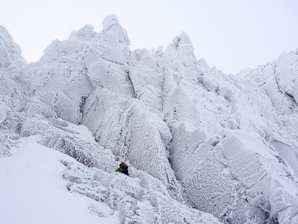 Lee Harrison moving up to the foot of Snuffleupagus (IV,6) in Coire an Lochain in the Northern Corries. The route follows the line of corners directly above Lee's head. (Photo Michael Barnard)