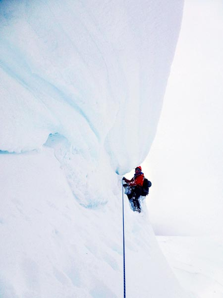 Sandy Allan climbing through the cornice on the first ascent of Risk of Ice (V,4) in Coire na Feola on Ben Wyvis. Current mountain hazards include large cornices, avalanche-prone slopes, warmer than forecast temperatures, and huge amounts of snow. (Photo Andy Nisbet)