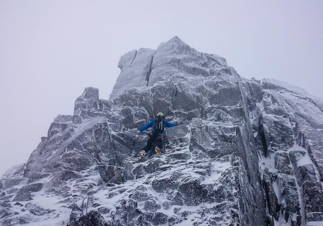 Ken Applegate starting the Direct Variation (IV,6) to Pinnacle Arête on Ben Nevis. The Direct Variation continues up the prominent offwidth crack up and left, whilst the original route climbs the chimney line on the right side of the photo. (Photo Steve Holmes)