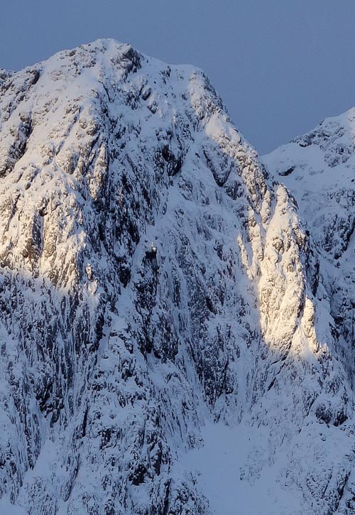 The upper section of the 400m-high Spider Buttress on Ladhar Bheinn in the Western Highlands. The much sought after Tir na Og (V,5) takes the central line of ice streaks and Face Route (IV,4) follows the line of grooves just left of the sunlit West Pillar. Tir na h-aoise (VI,6) climbs the barrel-shaped wall right of Tir na Og, starting up the tapering right-slanting gully. (Photo Simon Richardson)